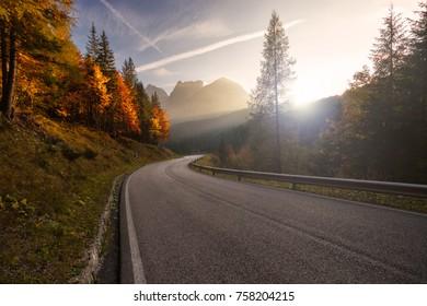 Deserted road leading to a mountain range during autumn season.