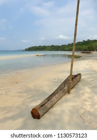 Deserted sandy beach on the tropical island of Koh Puos in Cambodia. Boat made by hollowing out a log on the sand. Shadows of the coastal trees.