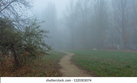The deserted sidewalk in the foggy city. Autumn city landscape. Garbage on lawns, Eastern Europe, ex USSR.