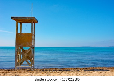 Deserted Spanish beach with lifeguard tower, against a clear blue sky looking down on to the Mediterranean Sea.