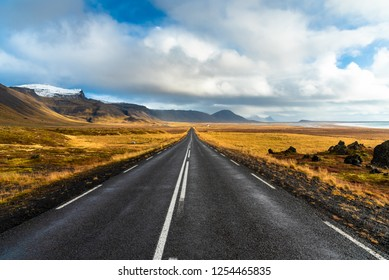Deserted Straight Road through Lava Fields and Volcanic Mountains in Iceland on a Sunny Autumn Day. The Coast and the Sea are Visible on the Right Side of the Picture