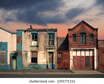 a deserted street of old abandoned ruined houses with bright peeling paint and crumbling brickwork in evening sunlight against a bright cloudy sunset sky redevelopment or fantasy concept