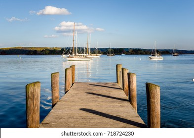 Deserted Wooden Jetty on Connecticut River at Sunset. Some Anchored Sailing Boats are visible in Background.