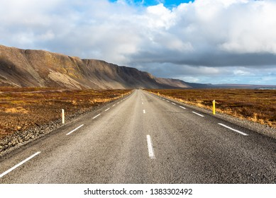 Desertedd Stretch of a Road Runnig at the Foot of Beautiful Mountains and Parallel to the Coast in Iceland on a Partly Cloudy Autumn Day.