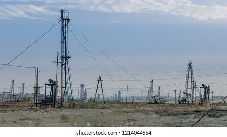 Desertous industrial landscape with oil pumps and rich modern city in background
