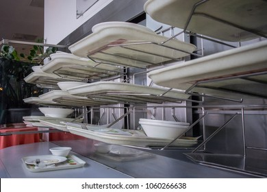 Deservicing conveyor belt for trays in a self service restaurant. Tray in a cafeteria on a belt which leads to cleaning facilities in the back of the restaurant.