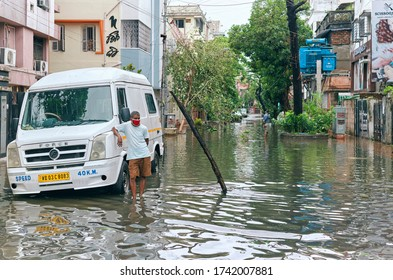 Deshapriya Park, Kolkata, 5/22/2020 : A municipal sewage worker standing in flooded street, next to an open sewer manhole. A log has been placed there, so no one accidentally fell into the manhole.