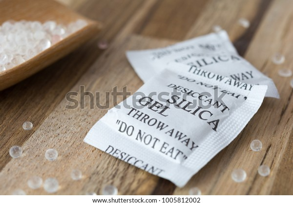 Desiccant or silica gel in white paper packaging and spread on the wooden background.
