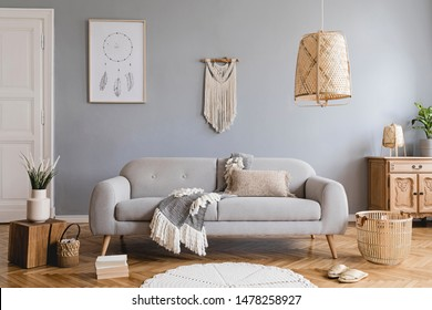 Design bohemian composition of living room interior with gray sofa, wooden cube, commode, beige macrame, rattan lamp ,plants, plaid, flowers and elegant accessories. Stylish home decor. Template.