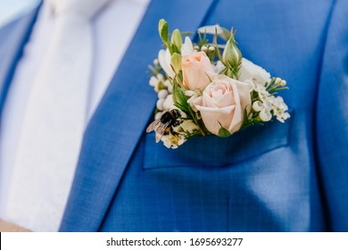 Design a boutonniere. Flowers in white, green and beige. Wedding day. Beautiful boutonniere of the groom. Blue suit.