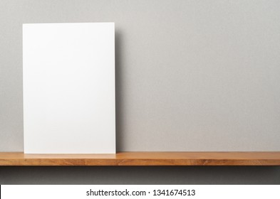 Design concept - front view of A4 hard paper stand on bookshelf and grey wall for mockup, not 3D render