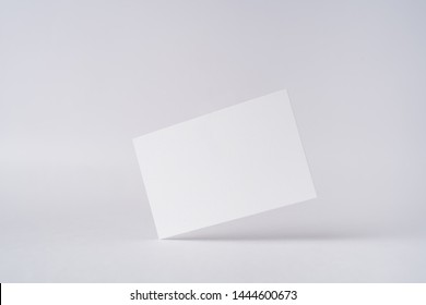 Design concept - front view of surreal white business card float on mid air isolated on white background for mockup, it's real photo, not 3D render