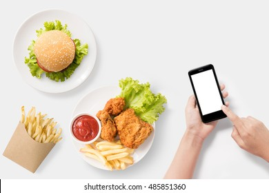Design concept of mock up Using smartphone with burger, french fries, fried chicken set isolated on white background. Copyspace for text and logo. Clipping Path included on white background.
