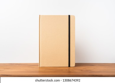 Design concept - Perspective view of kraft paper notebook on wood teak floor for mockup