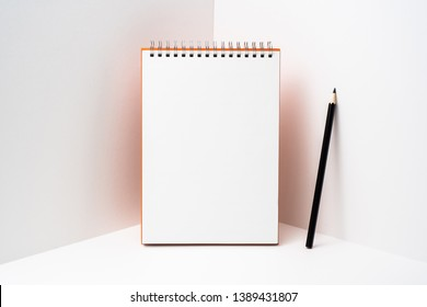 Design concept - perspective view of orange spiral notebook, white page on white 3D space background for mockup, it's real photo, not 3D render