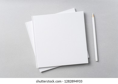 Design concept - Top view of 2 pure white notebook and pencil on grey background for mockup