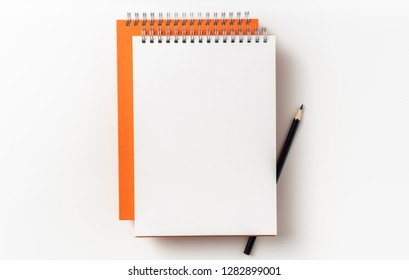 Design concept - Top view of 2 orange spiral notebook, white page and pencil isolated on background for mockup