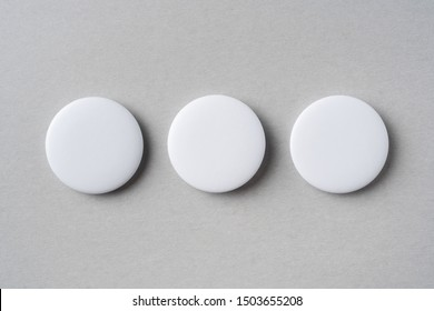 Design concept - top view of 3 white badge on grey background for mockup, it's real photo, not 3D render
