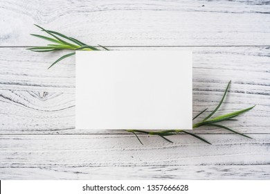 Design concept - top view of blank greeting card on white vintage wooden background for mockup