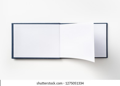 Design concept - Top view blue hardcover notebook with open & flip curl rolled page isolated on background for mockup