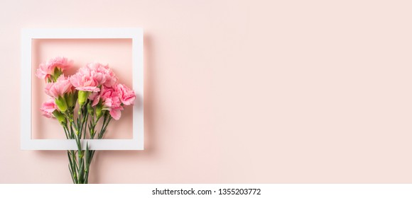 Design concept - top view of carnation with white square frame on pink background for mothers day, wedding and valentines day with copy space for mock up