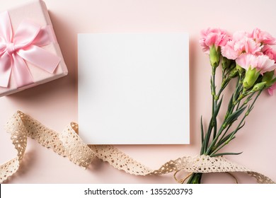 Design concept - top view of carnation and vintage ribbon, gift box and greeting card on pink background for mother day mockup