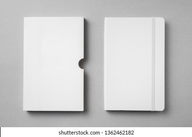 Design concept - top view of close white notebook with elastic band, case on grey background for mockup. real photo, not 3D render