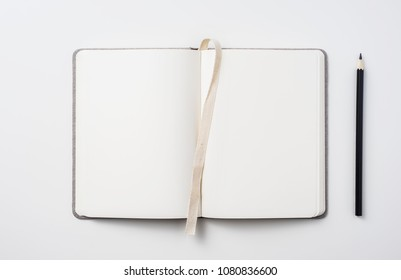Design concept - Top view of hardcover gray linen notebook with curl blank page and ballpoint pen isolated on white background for mockup