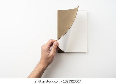 Design concept - Top view of man's hand hold high grade brown notebook isolated on white background for mockup series 6