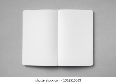 Design concept - top view of open white notebook with blank page isolated on grey background for mockup. real photo, not 3D render