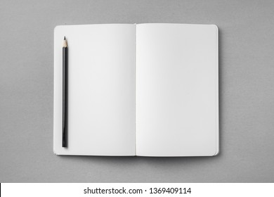Design concept - top view of open white notebook with blank page and wooden pencil on grey background for mockup. real photo, not 3D render