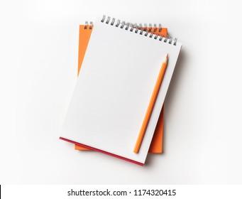 Design concept - Top view of orange and red spiral notebook and color pencil collection isolated on white background for mockup