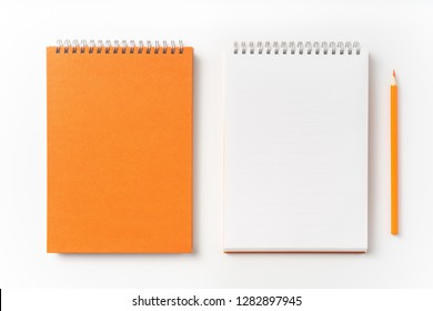Design concept - Top view of orange spiral notebook, white page and pencil isolated on background for mockup