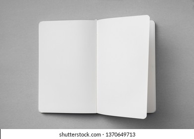 Design concept - top view of white notebook with blank open, turn and flipped page on grey background for mockup. real photo, not 3D render