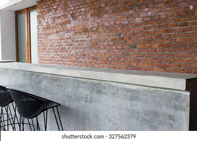 design of interior, counter bar made from cement with iron seat bar stool and brick wall background
