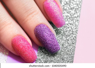 Design on long nails from multicolored sequin closeup.Nail art.