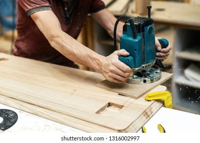 Design wood concept. Cropped photo of cabinetmaker handcraft man hands with electric tool make furniture in garage or workroom