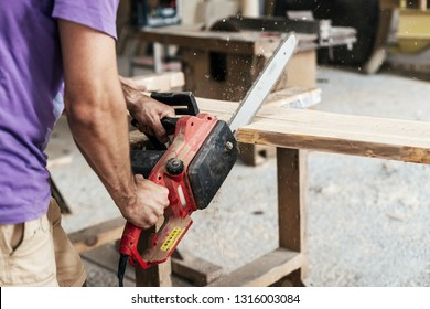 Design wood concept. Cropped photo of cabinetmaker or handyman holding chainsaw in hands sawing wood board make furniture in garage