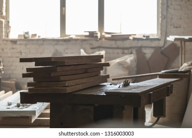 Design wood concept. Old fashioned rusty carpenters tools lying under wooden tile boards composition. Photo of wooden plank board on saw table in empty garage or workroom interior