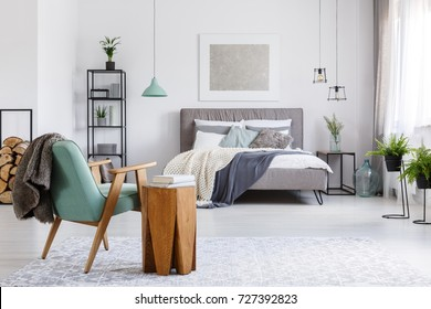 Design wooden table next to mint chair with fur in classic bedroom with silver painting and plants