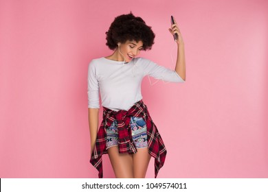 Design your dreams! African American smiling cheerful girl listening to music on her smartphone on the isolated pink background.
