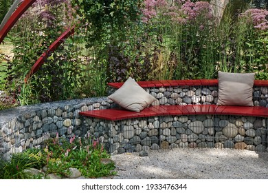 Designed Backyard Garden Patio and Outdoor Party Place. Modern Garden Design and Landscaping. Round Bench Made from Gabions with Wooden Seat. Landscaped Family Resting Area with Fireplace.
