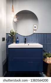 Designed bathroom with stylish blue cabinet and blue wall tiles