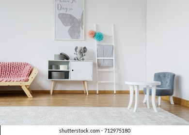 Designed blue chair near to wooden sofa with pink braided blanket in cozy room
