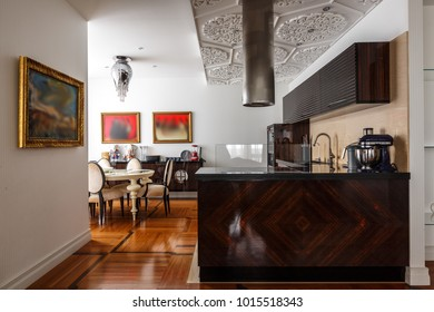 designed kitchen interior in luxury apartment, white walls, hardwood floor, stainless microwave and oven and coffee machine, stone countertop and marble on floor