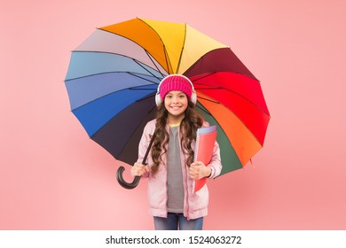 Designed for rainy weather. Little school girl hold colorful umbrella on pink background. Small child back to school in autumn. Adorable kid in earphones go to school on rainy day. The best school.
