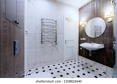 Designer bathroom with mirror, lamps, towel radiator, toilet and washbasin