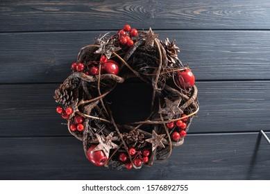 Designer christmas wreath on black wooden background.