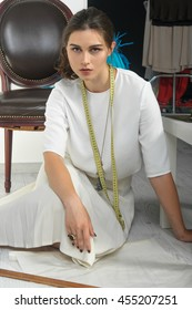 Designer clothes sitting on the floor coming up with clothes. She has brown hair and is wearing a light blouse. On her neck hangs a ribbon tape measure, and on the floor lay a pair of scissors.