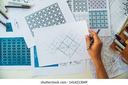 Designer designing drawing sketch pattern geometric flower seamless wallpaper fabric textile fashion industry. artistic design studio.